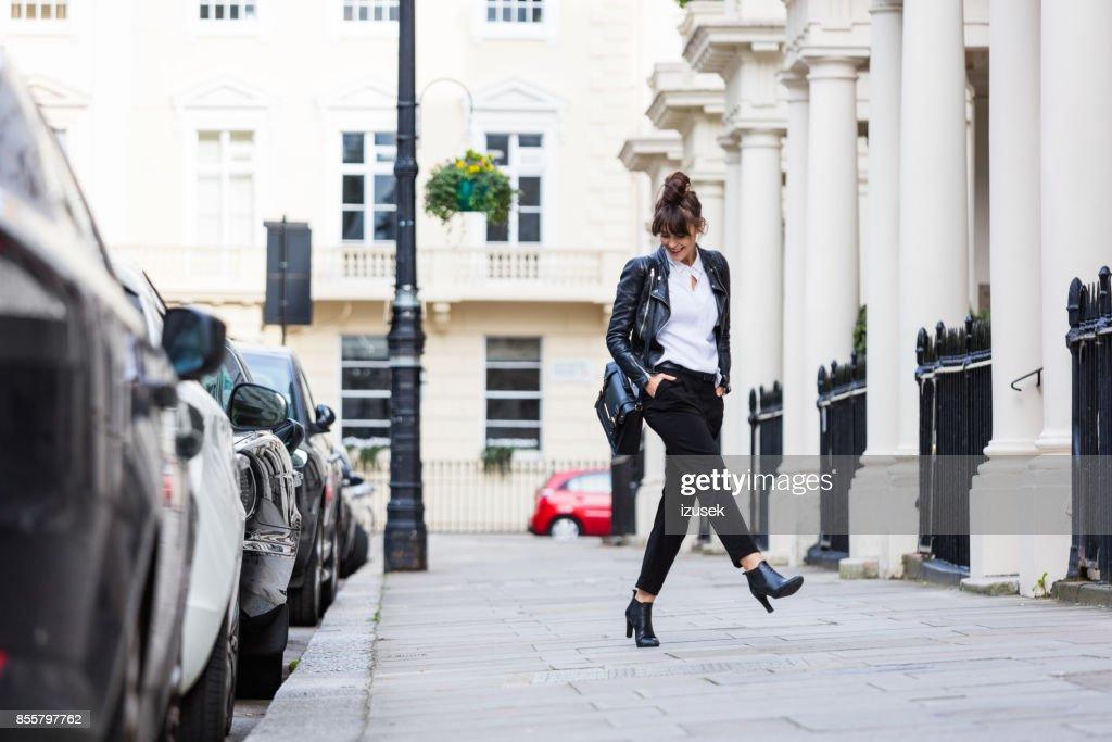Mujer feliz bailando en la calle de la ciudad : Foto de stock
