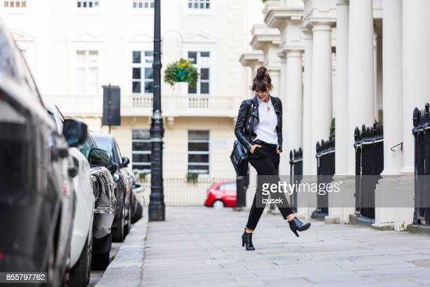 happy woman dancing in the city street - fashionable stock pictures, royalty-free photos & images