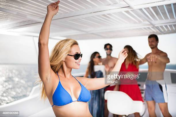 Happy woman dancing on a boat during summer day.