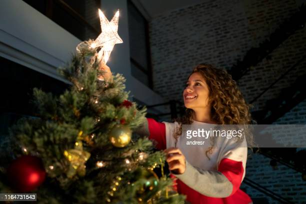 happy woman decorating her christmas tree and putting the star on top - decoration stock pictures, royalty-free photos & images