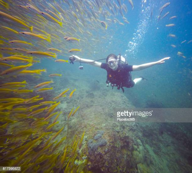 Happy Woman Diver in Shoal of Bigeye Snapper (Lujanus lutjanus) Fish