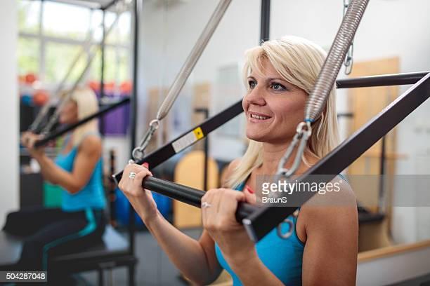 feliz mulher fazendo exercícios de pilates em uma academia de ginástica. - reformista - fotografias e filmes do acervo