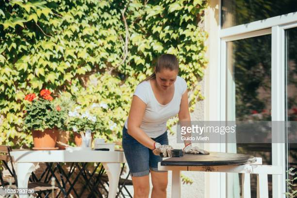 Happy woman doing upcycling with old table.