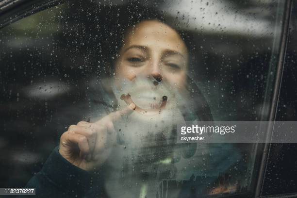 happy woman drawing smiley face on car window during rainy day. - smiley face stock pictures, royalty-free photos & images