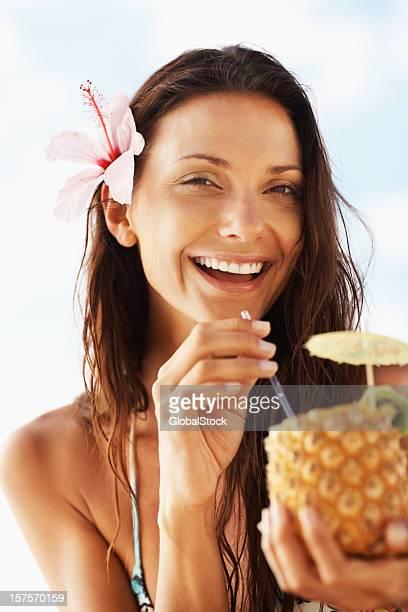 Happy woman drinking pineapple juice