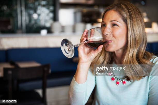 happy woman drinking red wine in restaurant - mid adult women stock pictures, royalty-free photos & images