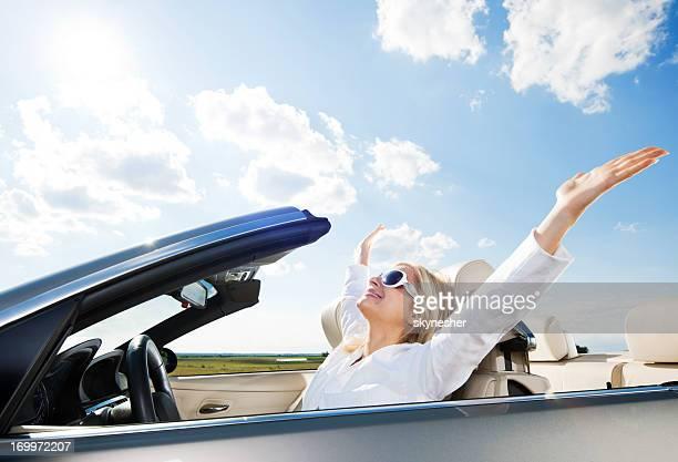 Glückliche Frau Fahren ein cabriolet-Auto.