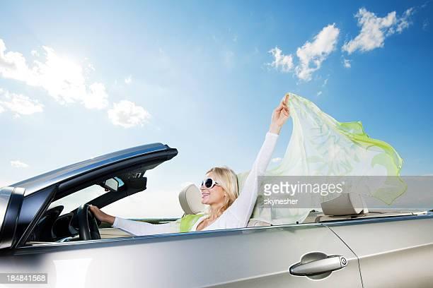 Happy woman driving a cabriolet car.