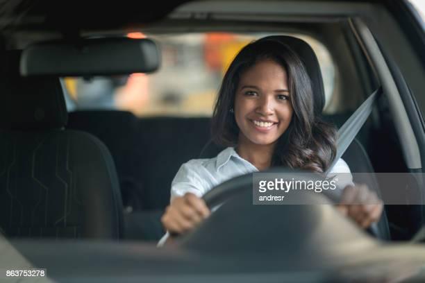 mulher feliz dirigindo um carro na concessionária ou na garagem - aluguel de carro - fotografias e filmes do acervo