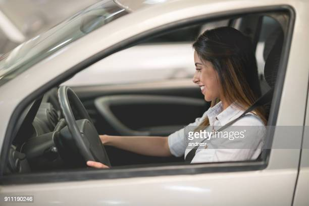 happy woman driving a car at the dealership or the garage - test drive stock pictures, royalty-free photos & images