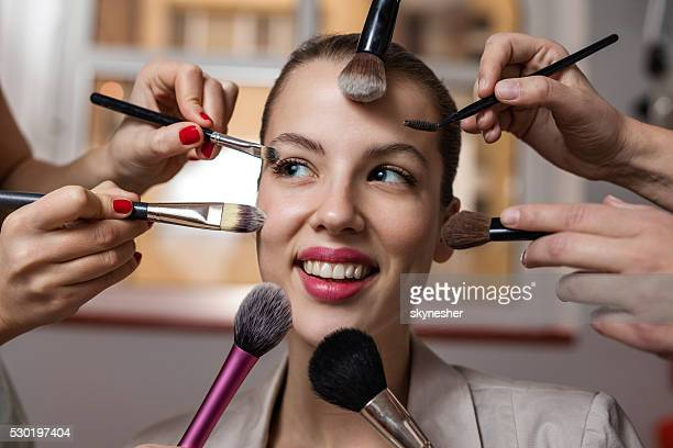 Happy woman during beauty treatment with make-up brushes.