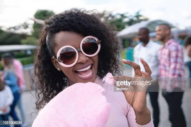 mujer feliz comiendo un algodón de azúcar en un parque de diversiones - carnaval evento de celebración fotografías e imágenes de stock