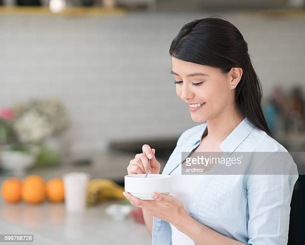 Happy woman eating breakfast at home