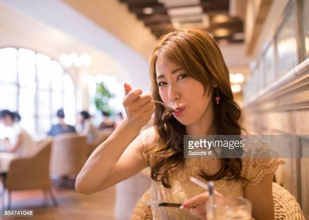 レストランでケーキを食べて幸せな女 - 30代の女性一人 ストックフォトと画像