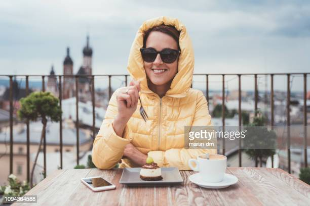 happy woman eating dessert with coffee on rooftop - malopolskie province stock pictures, royalty-free photos & images