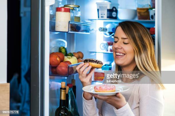 happy woman eating donuts from plate - caught in the act stock pictures, royalty-free photos & images