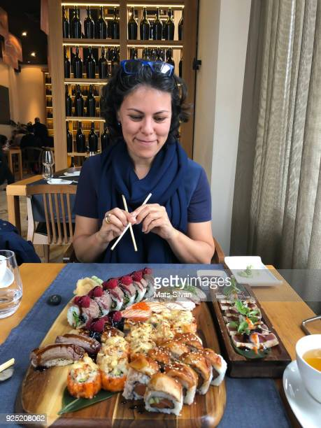 Happy Woman Eating in a Japanese Restaurant