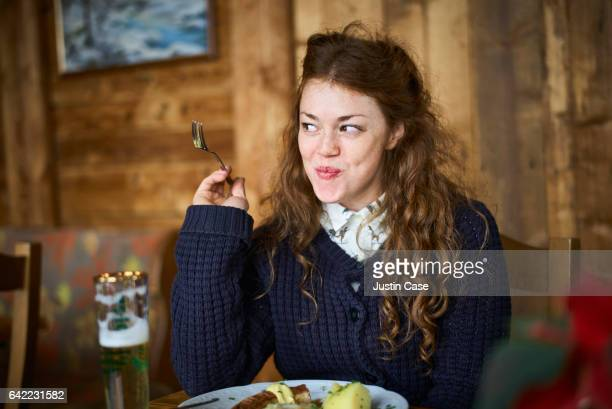 happy woman eating out in a restaurant - essen mund benutzen stock-fotos und bilder