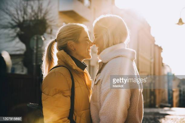 happy woman embracing female partner with closed eyes while standing in city - lesbisch lesbe lesben stock-fotos und bilder