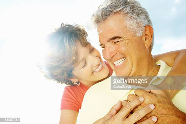 Happy woman embracing senior man from behind