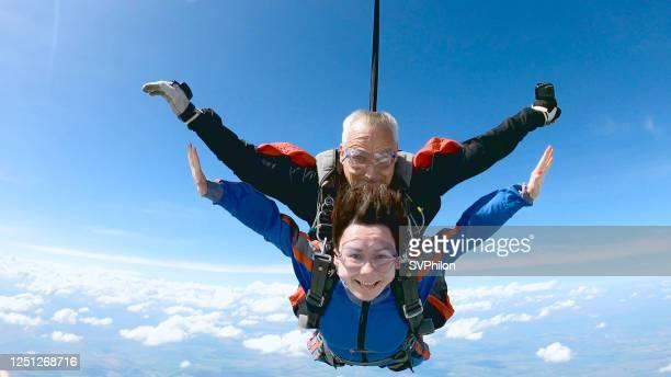 幸せな女性は経験豊富なパラシュートインストラクターと自由落下を楽しむ。 - 気が若い ストックフォトと画像