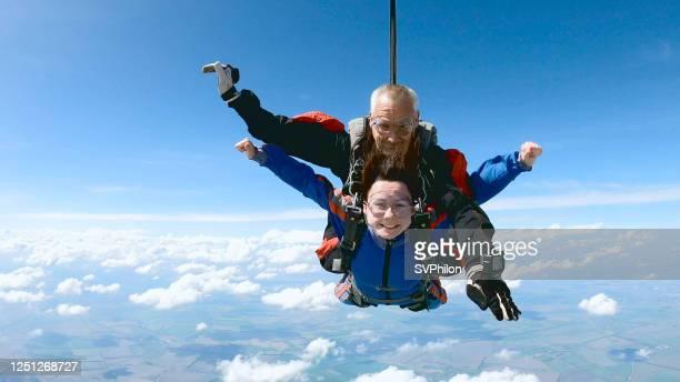glückliche frau genießen freien fall mit erfahrenen fallschirmspringer lehrer. - first occurrence stock-fotos und bilder