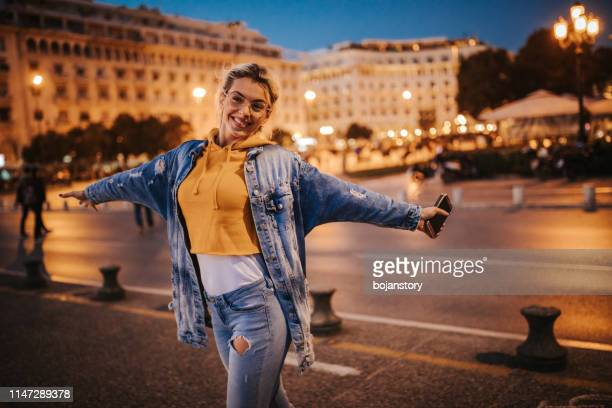 happy woman enjoying evening in the city - nightlife stock pictures, royalty-free photos & images