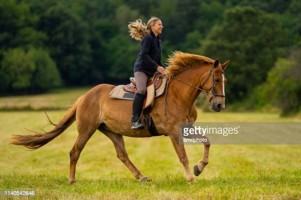happy woman enjoying galloping with her horse - andare a cavallo foto e immagini stock
