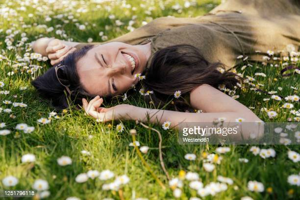 happy woman enjoying her free time while lying on grass with daisies - frühling stock-fotos und bilder