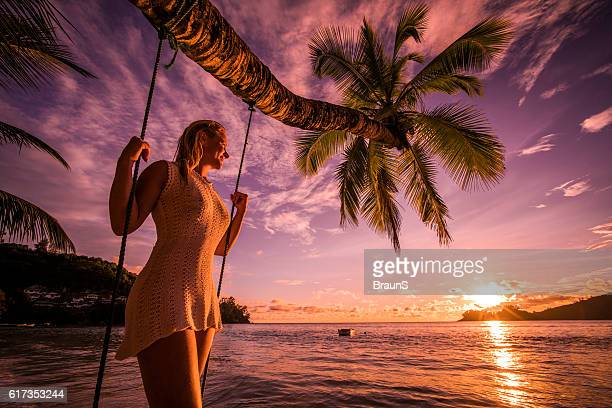 Happy woman enjoying in breathtaking sunset on the beach.