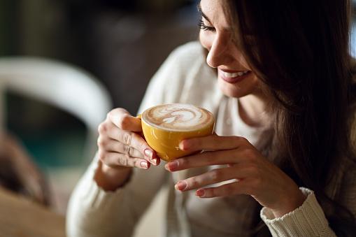 Happy woman enjoying in cup of fresh coffee. 1128647043