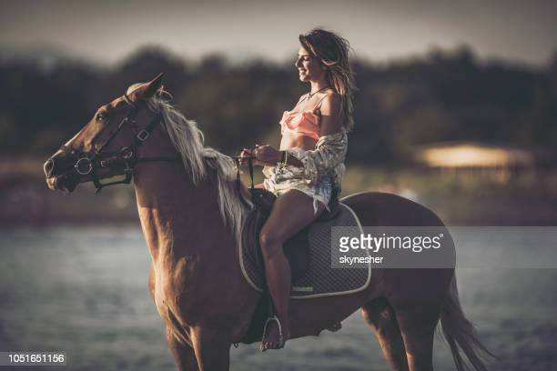 Happy woman enjoying in horseback riding with her eyes closed.