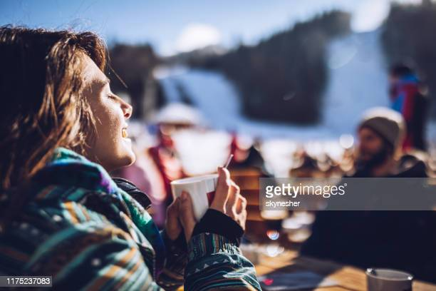 happy woman enjoying in sun and tea at ski resort. - sunny stock pictures, royalty-free photos & images