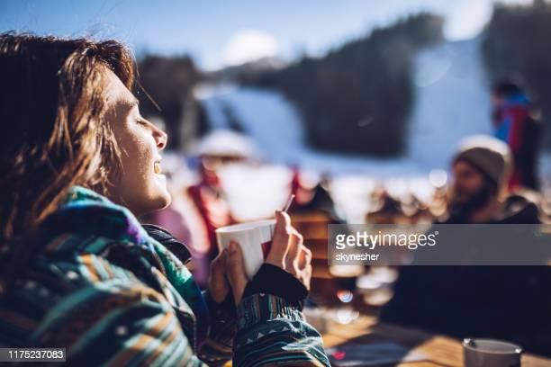 lycklig kvinna njuter i sol och te på ski resort. - solig bildbanksfoton och bilder