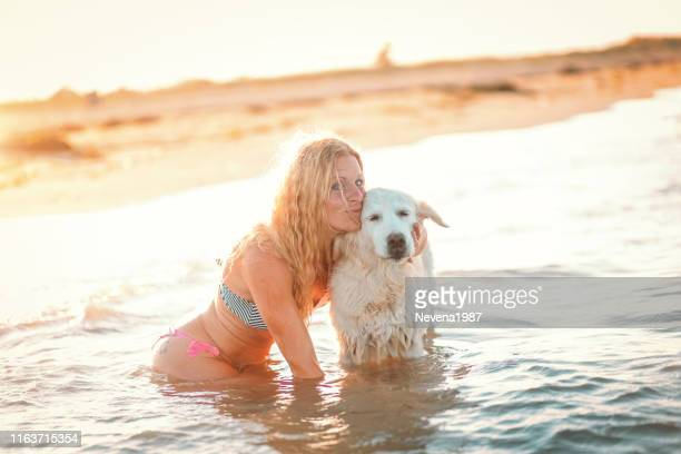 Happy woman enjoying in the sea with her dog.