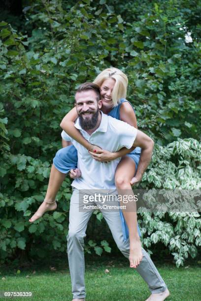 Happy woman enjoying piggyback ride on her boyfriend in garden, Bavaria, Germany