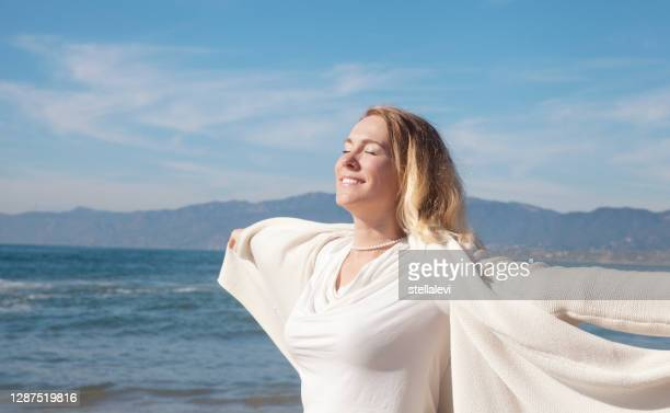 happy woman enjoying the sun at the beach - stellalevi stock pictures, royalty-free photos & images