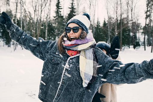 Happy woman enjoying with friend at snowy field - gettyimageskorea