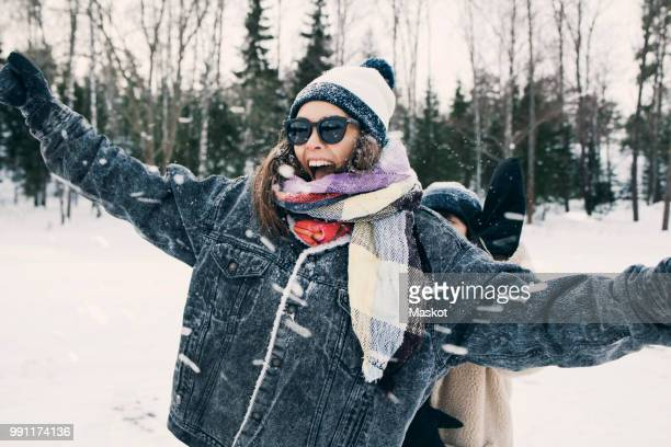 happy woman enjoying with friend at snowy field - warm clothing stock pictures, royalty-free photos & images