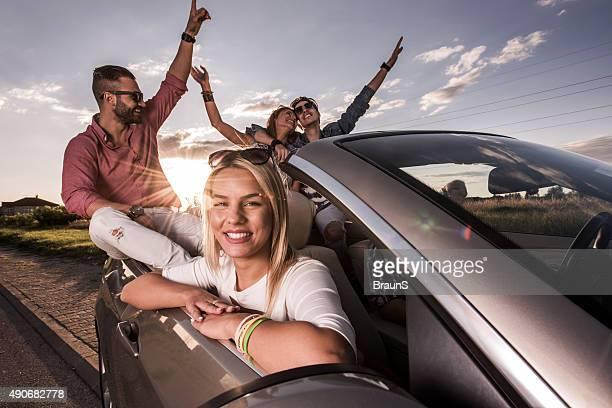 Donna felice godendo con i suoi amici in cabriolet al tramonto.
