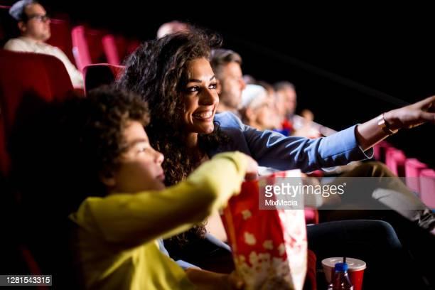 gelukkige vrouw die met haar zoon bij de bioskoop geniet - filmpremière stockfoto's en -beelden