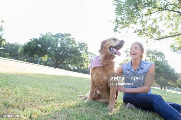 Happy woman enjoys a day in the park with her dog