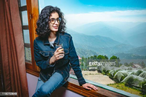 happy woman enjoys scenic view through holiday villa's window. - shimla stock pictures, royalty-free photos & images