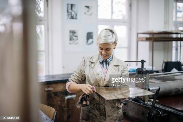happy woman enjoys working in her small printing atellier - lithograph stock pictures, royalty-free photos & images
