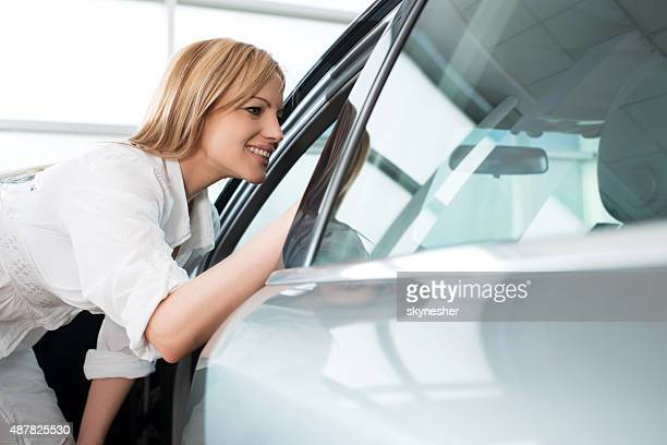 Happy woman examining a car in a showroom.