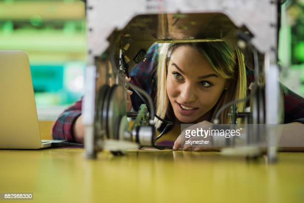 Happy woman examining a new robot in laboratory.