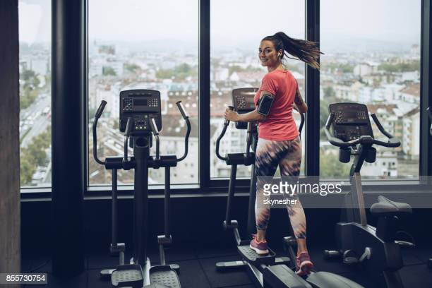 Happy woman exercising on a cross trainer in a gym.