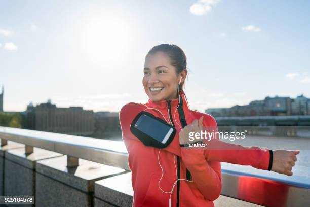 happy woman exercising outdoors and stretching - athleticism stock pictures, royalty-free photos & images