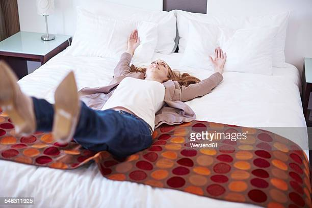 Happy woman falling backwards on hotel bed
