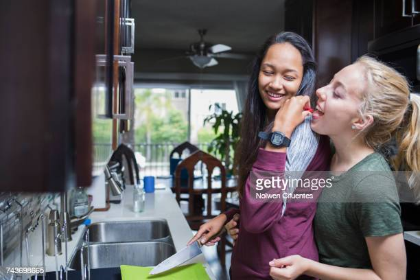 happy woman feeding another woman fruit in kitchen at home - cozinha doméstica imagens e fotografias de stock
